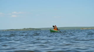 Professional kayaker in orange life jacket paddling a boat on the lake