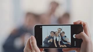 Rack focus from female hands holding smartphone and taking picture to group of schoolchildren in uniforms smiling and posing together