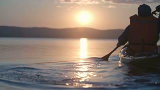 Rear view of silhouette of tourist skillfully paddling touring kayak at sunset and enjoying view