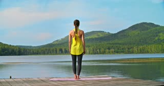 Rear view of woman performing a yoga tree pose facing a lake
