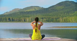 Rear view of woman sitting in lotus position near lake and doing breathing exercises