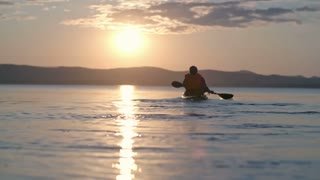 Rear view slow motion of tourist paddling with forward sweep strokes on touring kayak away from camera towards setting sun, silhouette of mountains visible in distance