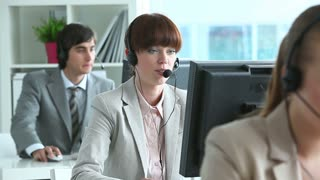 Row of call center operators in office with a pretty girl in the middle