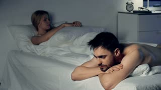 Sad young couple lying apart in bed at night sleepless and thoughtful