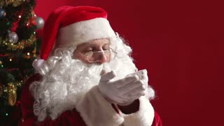 Santa Claus blowing glitter from his palms scattering it all around