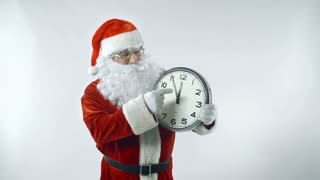 Santa Claus moving hands of clock forward up to midnight and laughing joyfully