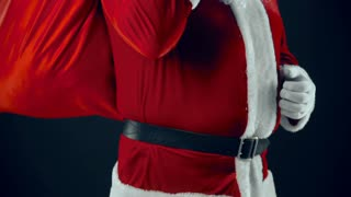 Santa Claus with sackful of Christmas presents dancing in the dark background in slow motion