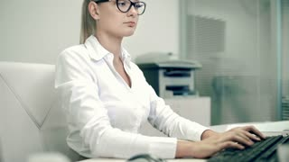 Secretary bringing documents to female boss busy typing on computer