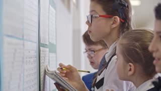 Selective focus of concentrated and serious schoolgirls and schoolboys in uniforms reading timetable and writing down lessons and time slots in their notebooks