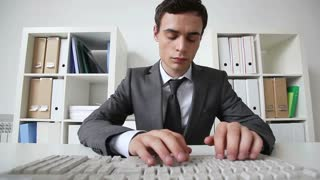 Serious office worker looking at the viewer and typing