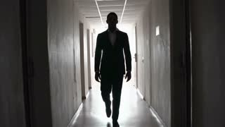 Shaky shot of man hastily approaching camera along the narrow dark passageway