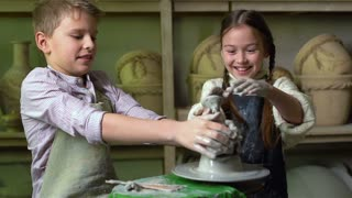Siblings having fun playing with clay on a pottery wheel