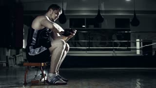 Side view of boxer winding handwrap around his wrist sitting in the darkness