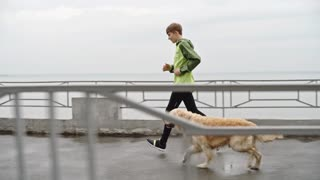 Side view of boy running with his dog in wet weather in slow motion