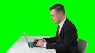 Side view of concentrated man in suit sitting against green screen background and typing fast on laptop