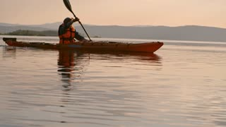 Side view of kayaker wearing lifejacket while rowing a boat on the lake in the evening