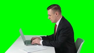 Side view of serious man in suit sitting against green screen background typing fast on laptop and looking at documents
