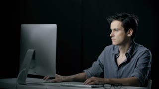 Side view of tired man getting down to work at computer in the black background
