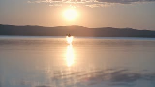 Silhouette of kayaker swimming towards the camera on the lake at scenic sunset