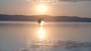 Silhouette of man rowing a kayak towards the camera on calm water at sunset