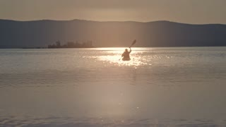 Silhouette of man rowing a kayak towards the camera on the lake with mountains in the background at sunset