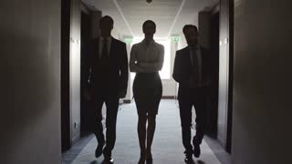 Silhouettes of two businessmen and businesswoman walking towards the camera through dark corridor in hotel in slow motion