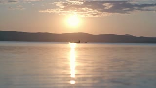 Slow motion lockdown of setting sun reflecting on lake water with silhouette of tourist on touring kayak enjoying view