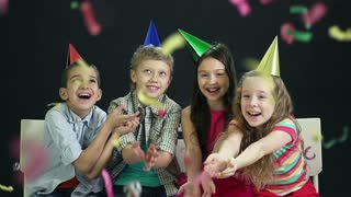 Slow-motion of children having fun at party catching falling confetti