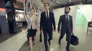 Slow motion of three business people approaching camera, two colleagues joining them in the airport terminal