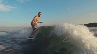 Slow motion of windsurfer gliding along waves and jumping