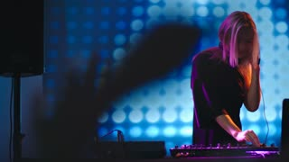 Slow motion of young blond DJ woman dancing behind mixing console at party in nightclub, LED video wall in background