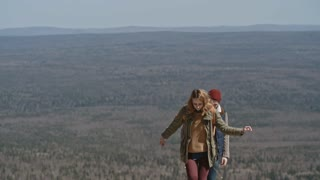 Slow motion of young blond woman and her bearded boyfriend climbing rocky ledge on hiking trip then checking direction on mobile phone