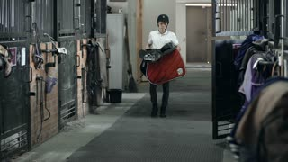 Slow motion of young jockey approaching camera strolling through the stable with tack