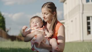 Slow motion of young mother sitting on green grass and playfully rocking her laughing toddler girl