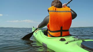 Slow motion rear view of male tourist in life jacket paddling with forward sweep strokes along blue away from camera