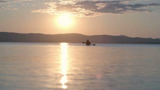 Slow motion rear view of sunset over tranquilly flowing lake with silhouette of tourist kayaking in distance