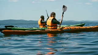 Slow motion rear view tracking of male and female athletes paddling kayaks along beautiful lake and looking at magnificent view of mountains