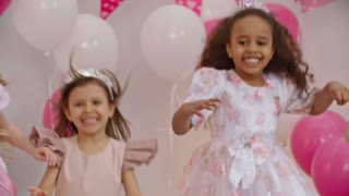 Slow motion shot of four little girls dressed like princesses jumping on sofa decorated with balloons and laughing