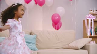 Slow motion shot of little African girl in princess crown and dress dancing and spinning with outstretched arms in room decorated with balloons