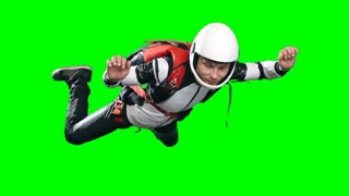 Slow motion shot of professional skydiver turning in free fall, man in full parachuting gear helmet, jumpsuit and harness, chroma key against green screen background