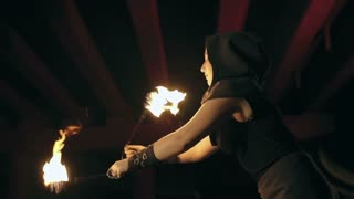 Slow motion shot of woman performing risky trick during fire show at night