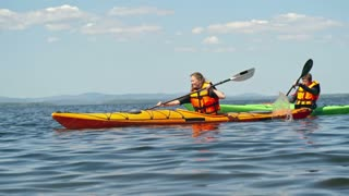 Slow motion tracking of female and male athletes paddling kayaks across blue water surface racing each other