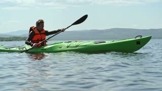 Slow motion tracking of man with beard forward sweeping on his kayak across blue lake