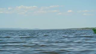 Slow motion tracking of middle aged tourist with beard paddling kayak on blue lake on sunny summer morning