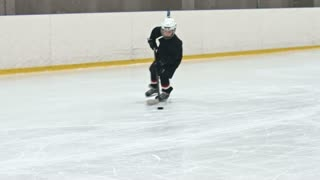 Slow motion tracking of novice forward player hitting puck towards opposing teams net and failing to score as little goalie making save with butterfly technique