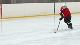 Slow motion tracking of novice ice hockey forward tricking opposite teams player and scoring goal
