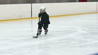 Slow motion tracking shot of novice ice hockey player dribbling puck and failing to score goal as defenseman from opposite team leg checking him