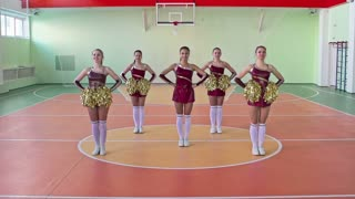 Slow-motion video of five young beautiful cheerleader girls performing in formation of circle smiling brightly and looking at camera during practice in school gym with pom-poms