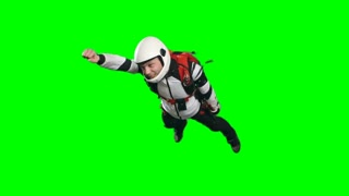 Slow motion video of smiling parachutist man in white helmet and gear flying free fall with his arm forward in superhero pose, side and front view chroma key against green screen background