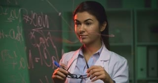 Smiling girl in lab coat standing behind the glass wall and writing formula on it